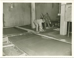 Local workers smooth concrete in additions.